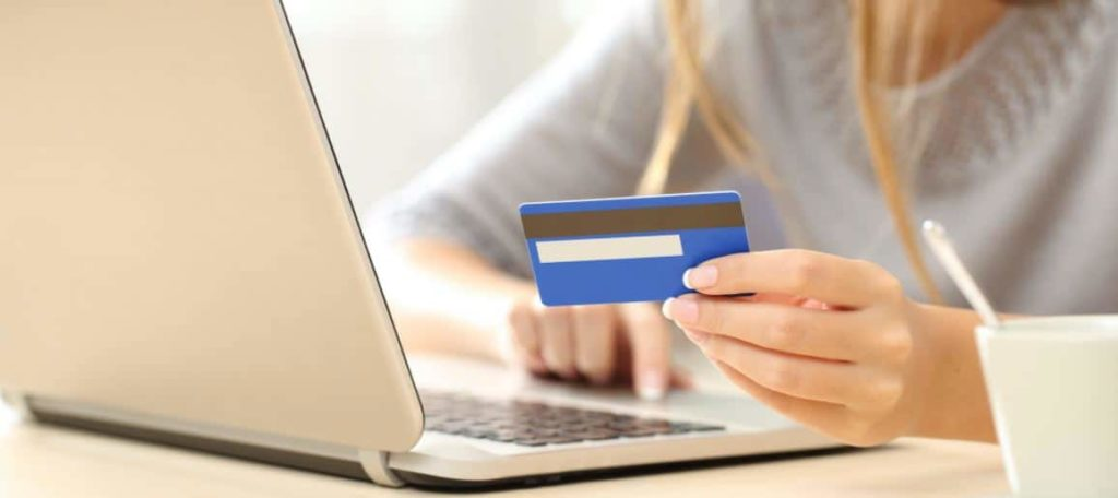 woman holding credit card with laptop