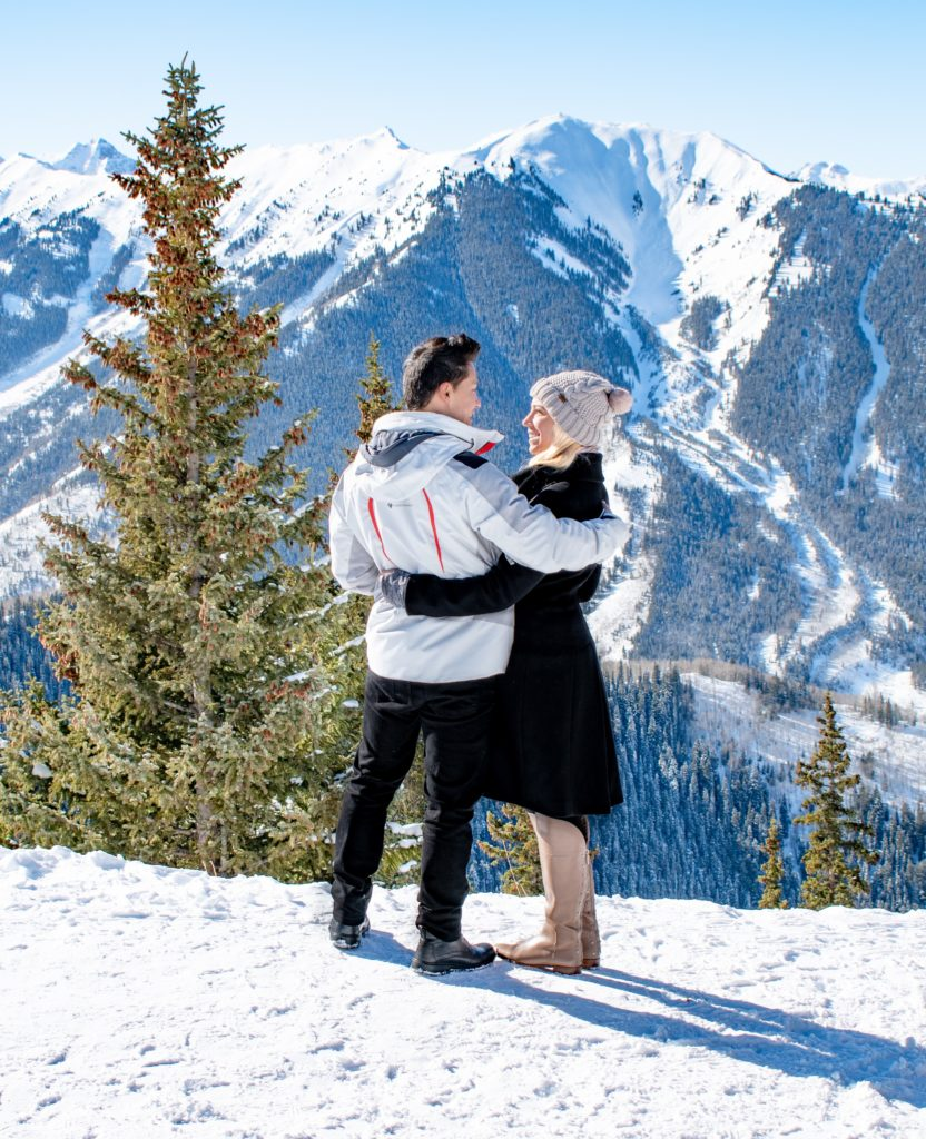 a couple admiring the views of the highland bowl from aspen peak